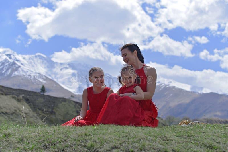 Eine junge Frau mit zwei T?chtern in den roten Kleidern, die im Fr?hjahr in den Schnee-mit einer Kappe bedeckten Bergen stillsteh stockfotos