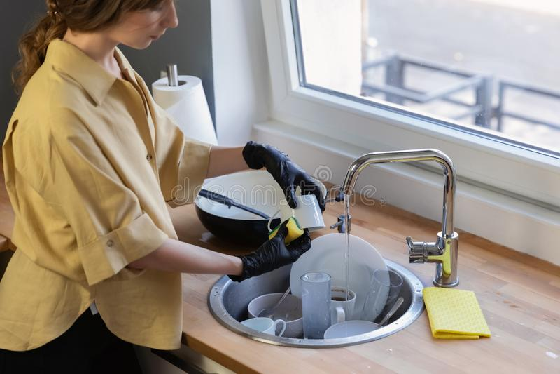 Eine junge Frau räumt in die Küche auf und wäscht Teller lizenzfreie stockfotografie