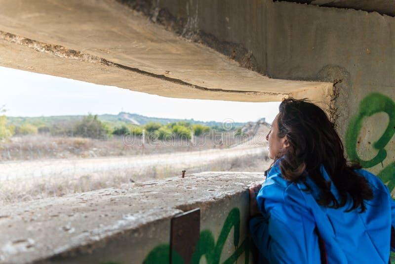 Eine junge Frau schaut durch den Embrasure in einem konkreten Sicherheitstrennungszaun auf der Grenze zwischen Israel und dem Lib stockbilder