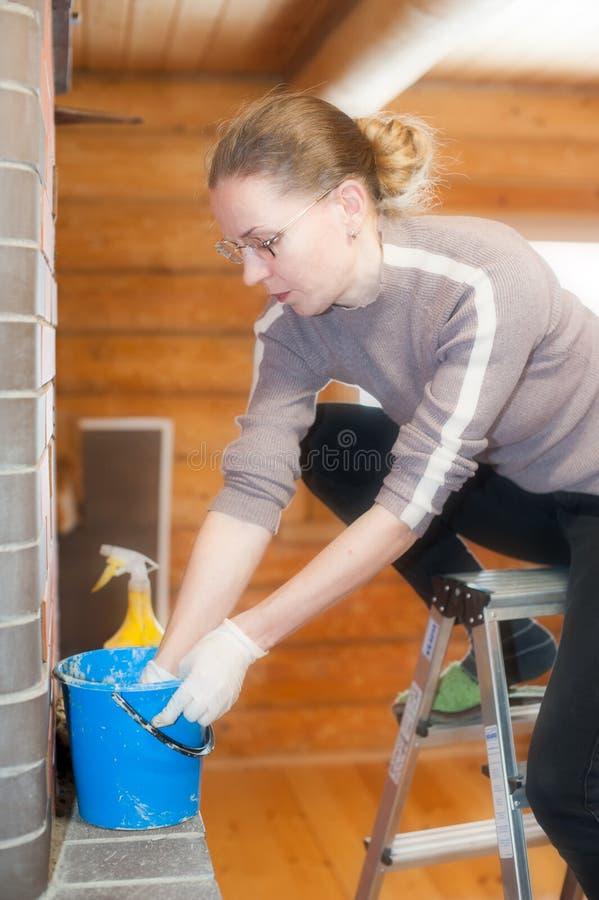 Eine junge Frau schmiert den Lehm in einem klaren Ofen, der auf einer tragbaren Leiter sitzt lizenzfreies stockfoto