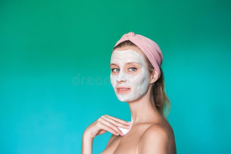 Eine junge Frau setzt eine weiße Maske auf ihr Gesicht mit ihren Händen Schönheitsfoto einer Frau mit einer hellen Maske auf ihre stockfoto