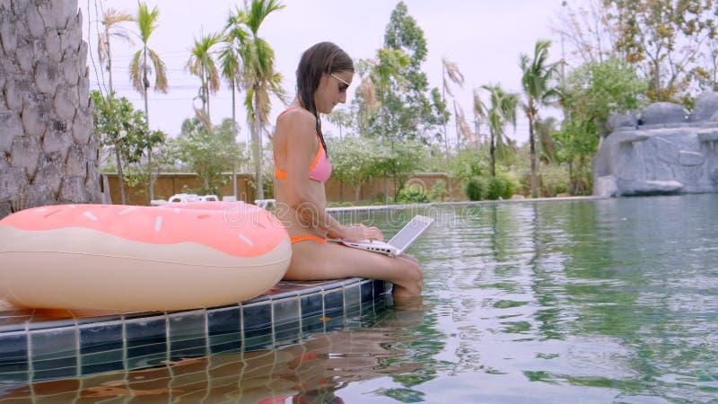 Eine junge Frau sitzt durch das Pool mit Minicomputer Selektiver Fokus stockfotos