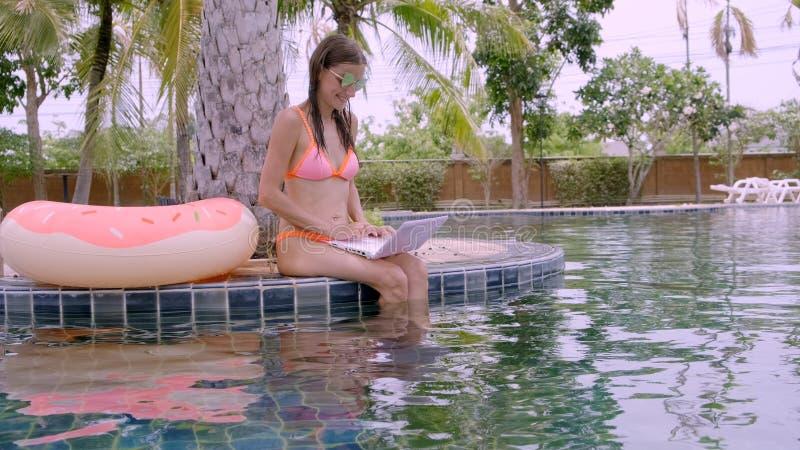 Eine junge Frau sitzt durch das Pool mit Minicomputer Selektiver Fokus stockbilder