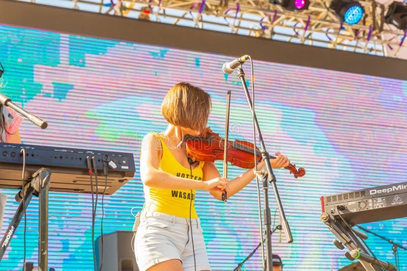 Eine junge Frau spielt die Violine auf einem offenen Sommerstadium lizenzfreie stockfotografie