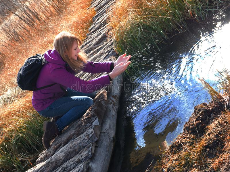 Eine junge Frau spielt mit Wasser in einem Nebenfluss Sun-Strahlen auf dem Spray des Wassers stockfotos