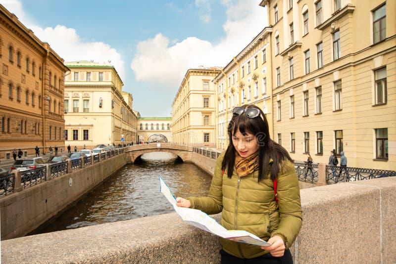 Eine junge Frau steht auf einer Brücke auf dem Damm des Moika-Flusses mit Blick auf die Einsiedlerei in St Petersburg und ist stockfotografie