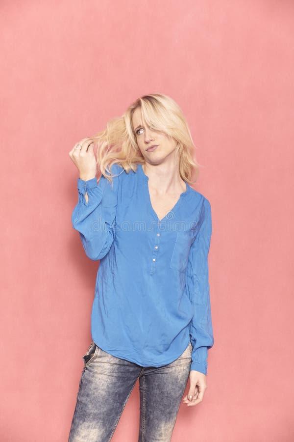 Eine junge Frau, unzufrieden gemacht ?ber ihr Haar, 20-29 Jahre alt, lang blondes Haar lizenzfreie stockbilder