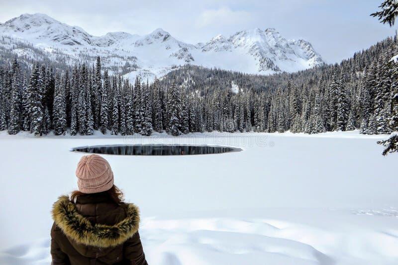 Eine junge Frau, welche die schneebedeckten Ansichten von Island See in Fernie, Britisch-Columbia, Kanada bewundert Der majestäti lizenzfreie stockfotografie
