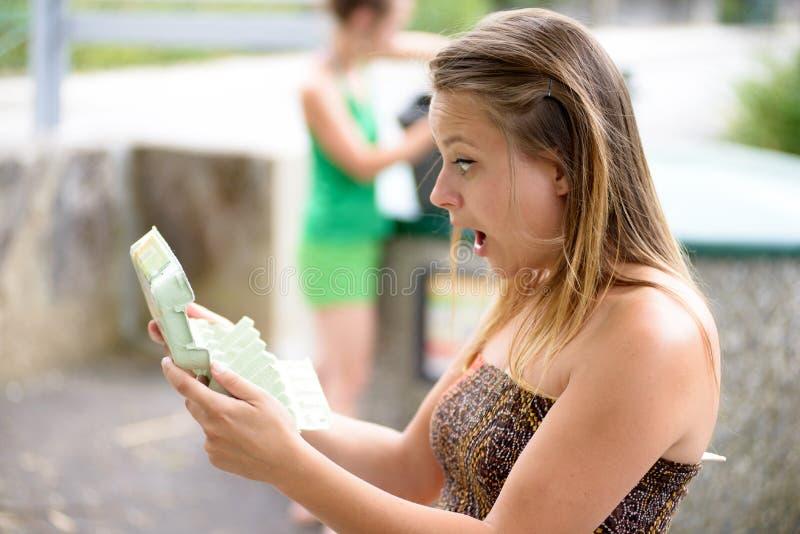 Eine junge Frau wird überrascht, indem man einen Kasten öffnet lizenzfreie stockfotos