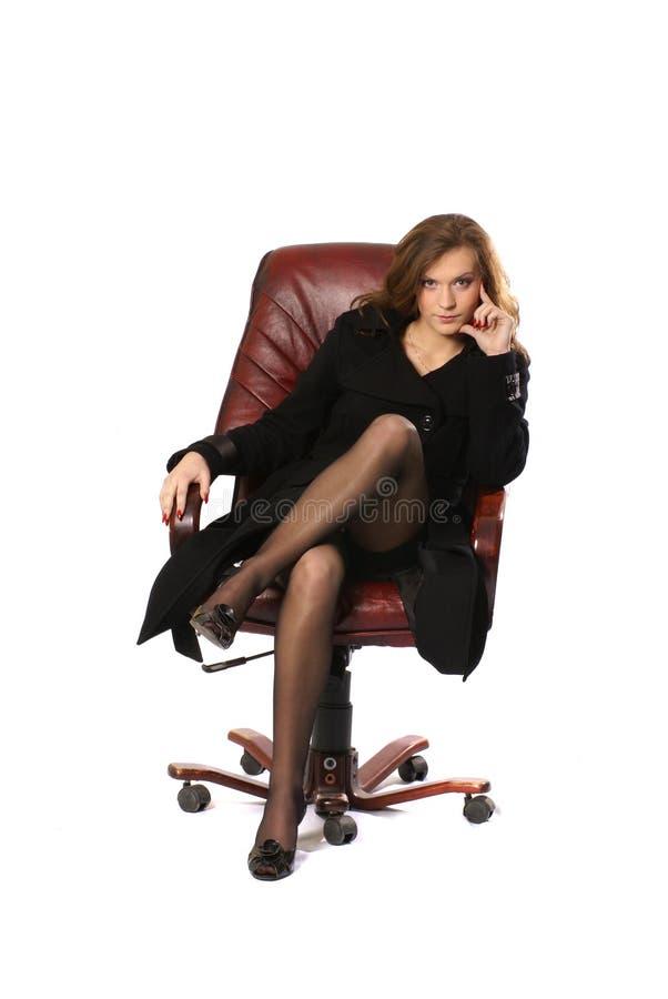 Eine junge Geschäftsfrau, die in einem ledernen Stuhl sitzt lizenzfreies stockbild