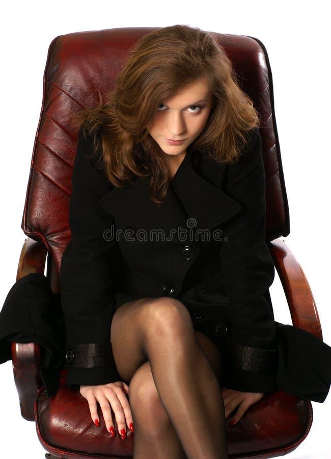 Eine junge Geschäftsfrau, die in einem ledernen Stuhl sitzt lizenzfreie stockbilder