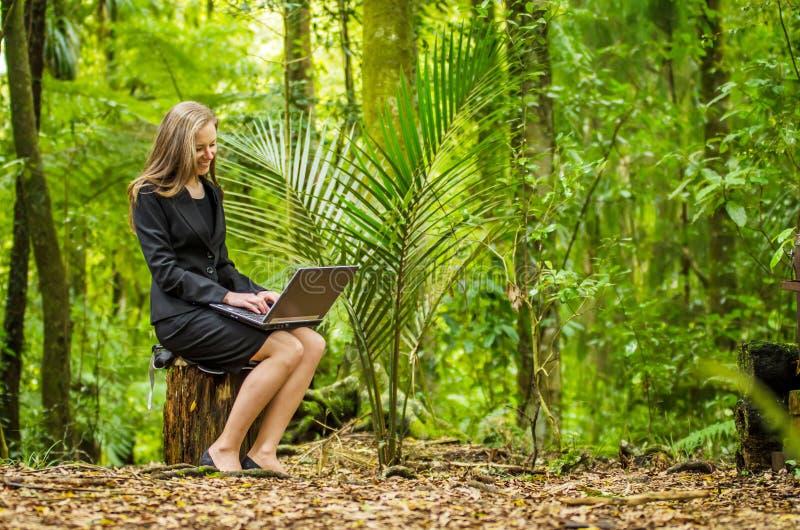 Eine junge Geschäftsfrau, die an ihrem Laptop im Wald arbeitet stockfoto