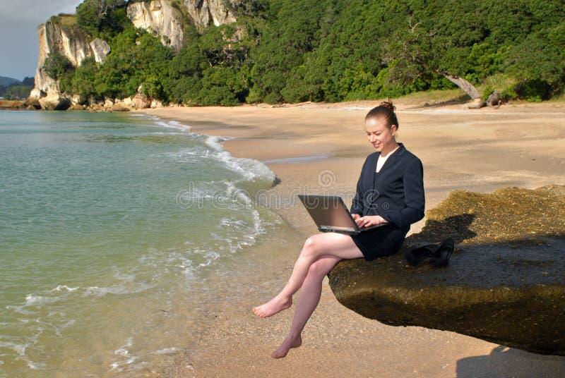 Eine junge Geschäftsfrau, die an ihrem Laptop am Strand arbeitet lizenzfreie stockbilder
