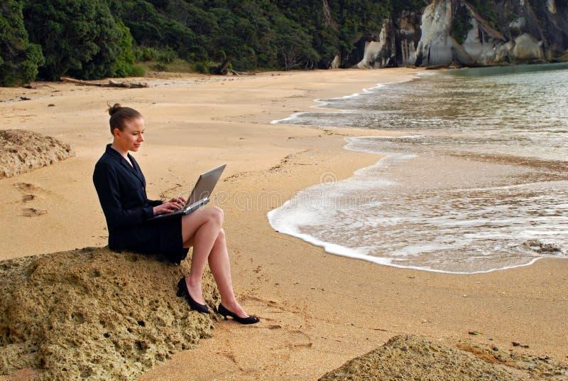 Eine junge Geschäftsfrau, die an ihrem Laptop am Strand arbeitet stockfotos