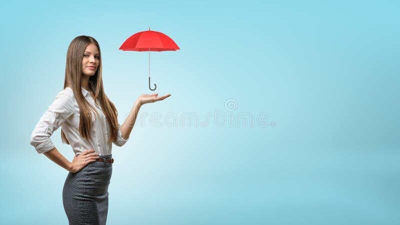 Eine junge Geschäftsfrau stützt einen kleinen offenen roten Regenschirm auf seiner offenen Palme lizenzfreies stockfoto