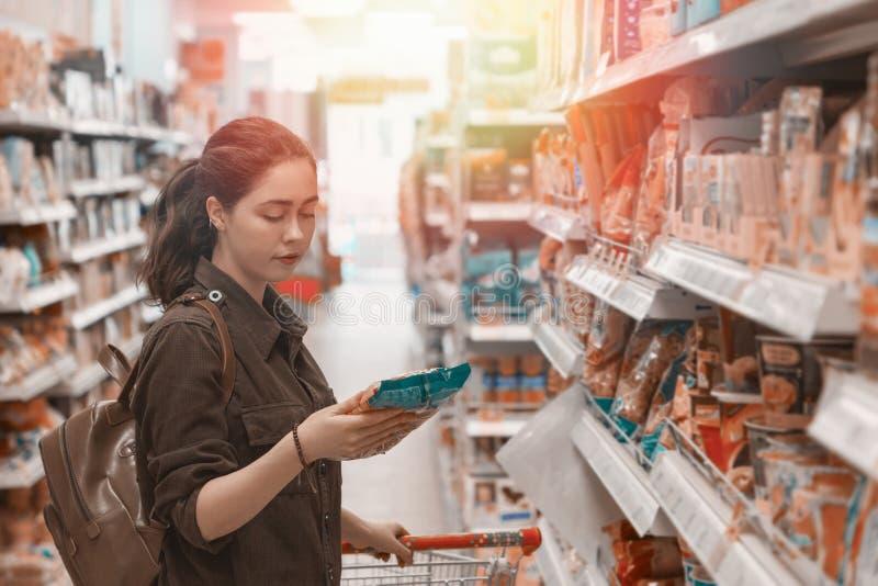 Eine junge h?bsche Frau h?lt einen Lebensmittelgesch?ftwagen und w?hlt sorgf?ltig die Produkte im Speicher leuchte Abschluss oben stockbild