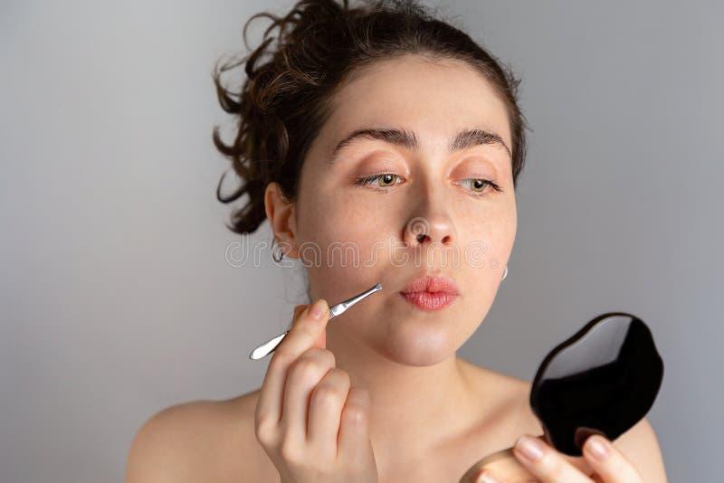 Eine junge hübsche Frau schaut in einem kompakten Spiegel und zieht ihre Antennen mit Pinzette aus Das Konzept des Loswerdens une stockbild