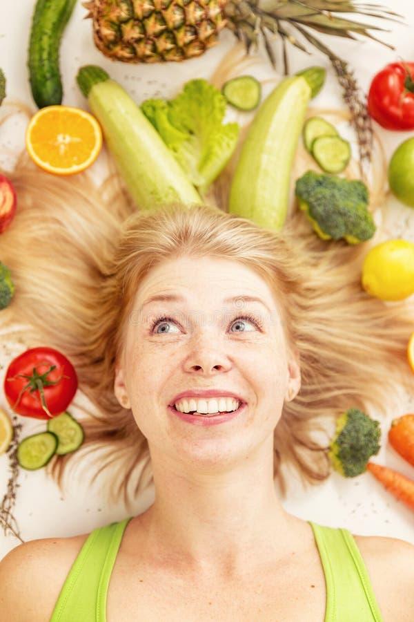 Eine junge hübsche Frau umgeben durch Gemüse und Früchte lizenzfreie stockfotografie