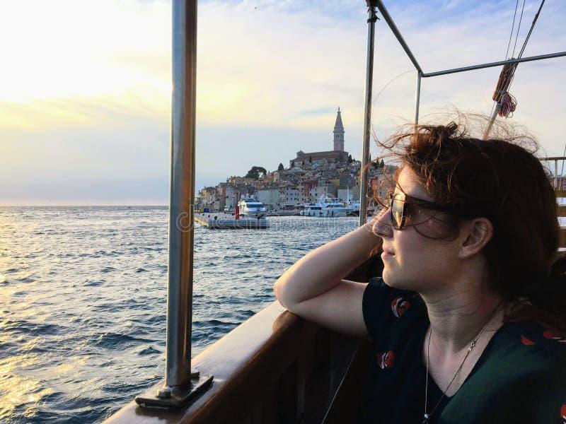 Eine junge hübsche Frau, welche die schönen Ansichten des adriatischen Meeres während des Sonnenuntergangs außerhalb der alten St stockfoto