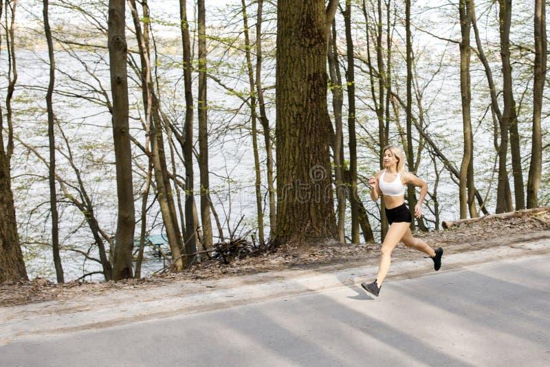Eine junge, hübsche Mädchenblondine läuft draußen im Wald nahe dem See mit schöner Landschaft Tr?gt T?tigkeit zur Schau ?bung stockbilder