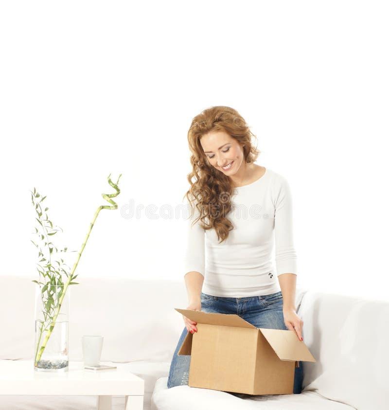 Eine junge kaukasische Frau, die einen Kasten auf einem Sofa anhält stockfoto