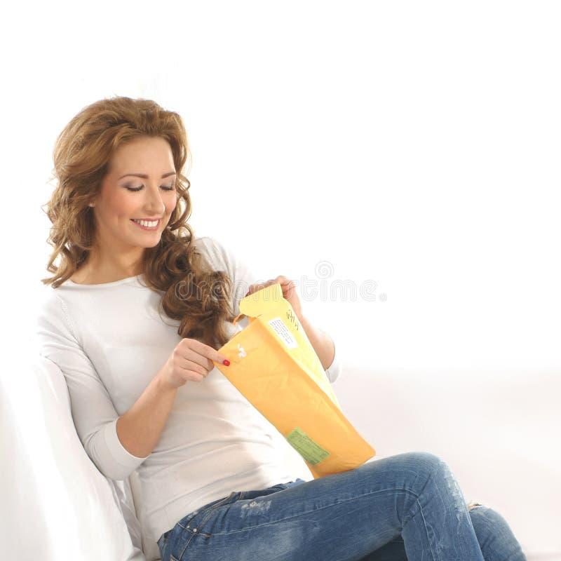 Eine junge kaukasische Frau, die einen Papierkasten öffnet lizenzfreie stockfotos