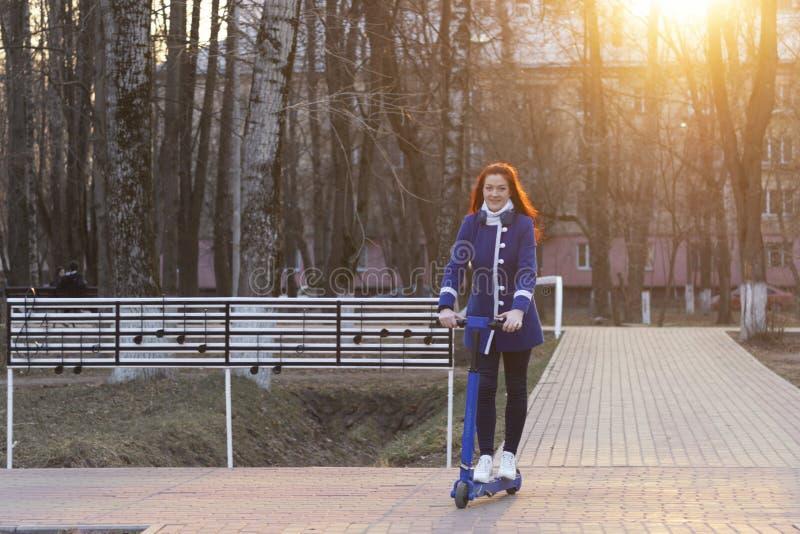 Eine junge kaukasische Frau mit dem roten Haar in einem blauen Mantel schnell rollt oder reitet einen blauen elektrischen Roller  stockfotografie