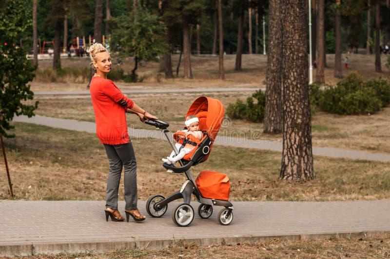 Eine junge lächelnde Mutter trägt einen orange Spaziergänger mit einem Baby im Park lizenzfreies stockfoto