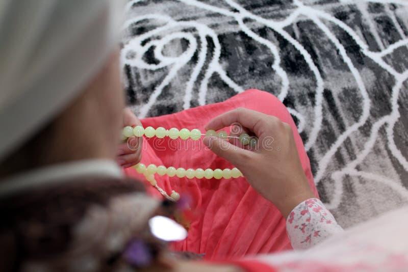 Eine junge moslemische Frau f?hrt Gebet in der Moschee durch stockfotografie