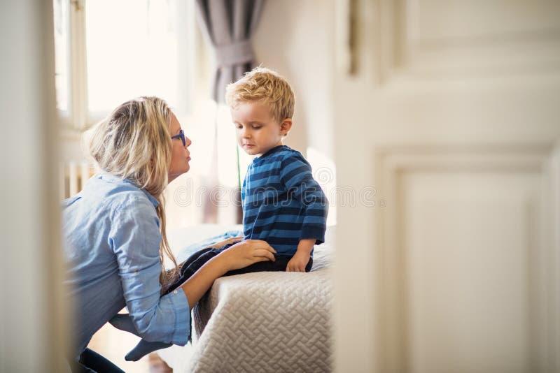 Eine junge Mutter, die mit ihrem Kleinkindsohn nach innen in einem Schlafzimmer spricht stockbild