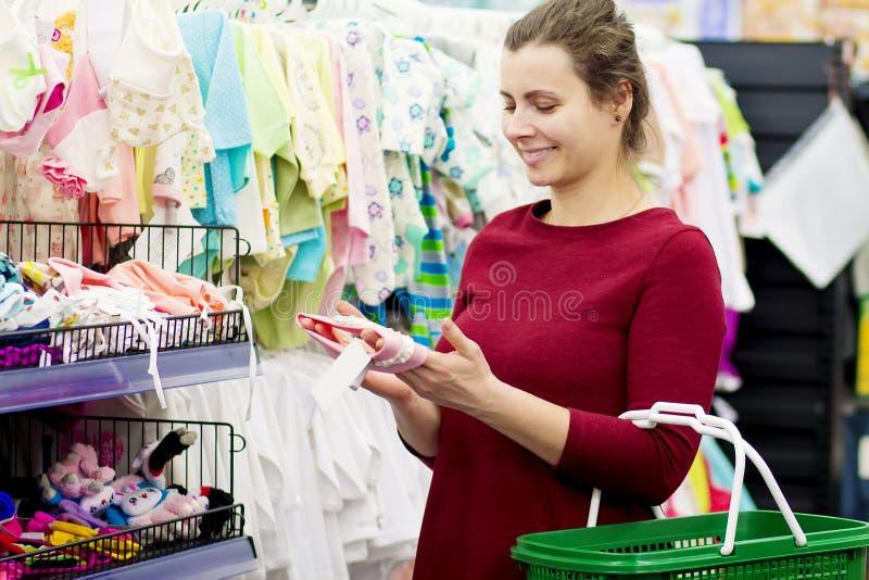 Eine junge Mutter kauft Kleidung für ihr Baby in einem Kind-` s Bekleidungsgeschäft Das Mädchen wählt Kleidung im Mall lizenzfreie stockbilder