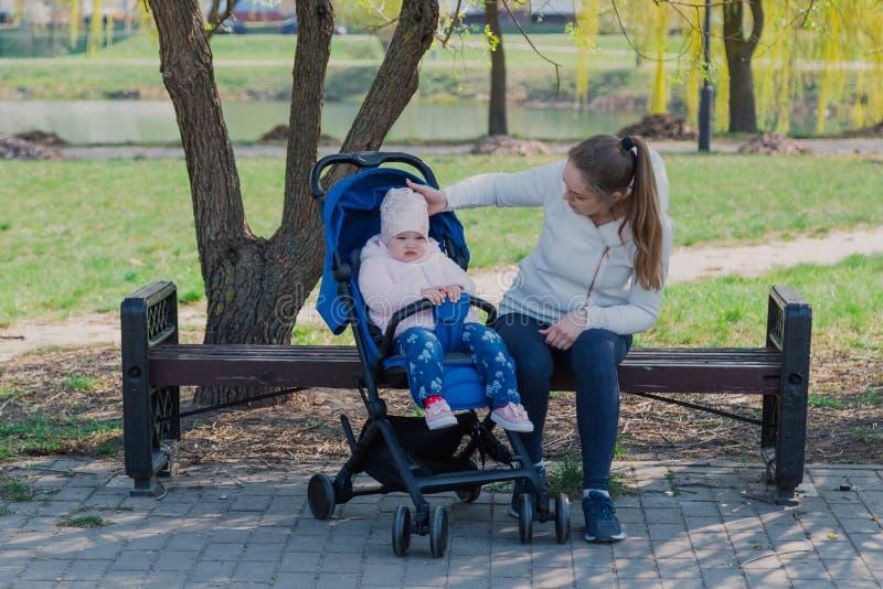 Eine junge Mutter mit einem Baby in einem Pram sitzt auf einer Bank an einem sonnigen Tag lizenzfreie stockbilder