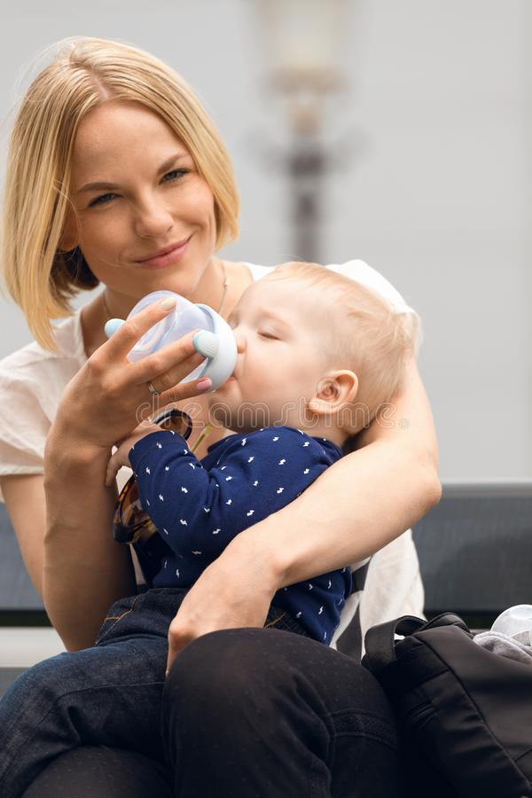 Eine junge Mutter sitzt auf einer Bank in der Straße und im Wasser ihr Baby von der Flasche stockfotografie