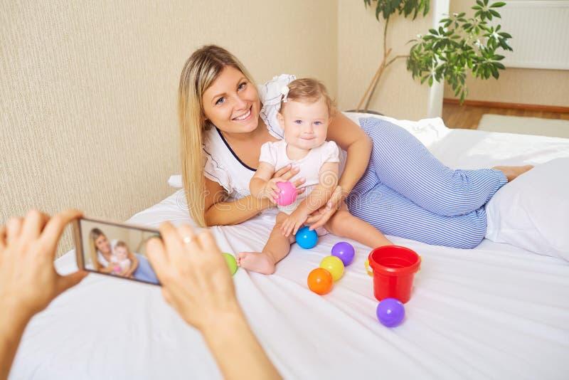 Eine junge Mutter wird mit ihrem Baby fotografiert lizenzfreies stockfoto