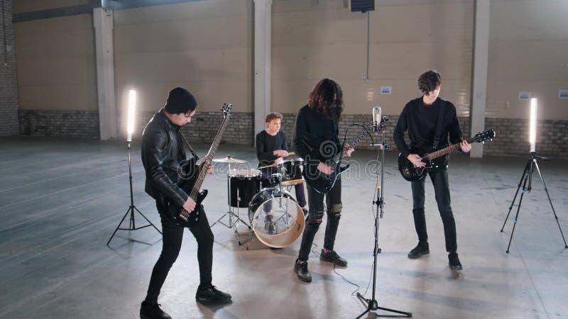 Eine junge Rockgruppe, die eine Wiederholung in einem Hangar hat Mitglieder einer Gruppe, die schwarze Kleidung trägt lizenzfreie stockfotografie