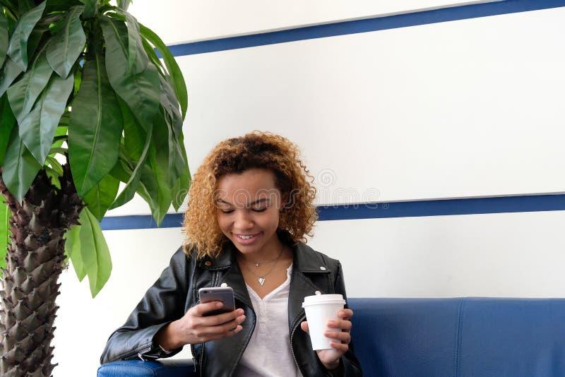 Eine junge schöne Afroamerikanerfrau in einer Lederjacke mit einem Weißbuchglas, das auf einem blauen Sofa nahe einer Palme sitzt stockfotos