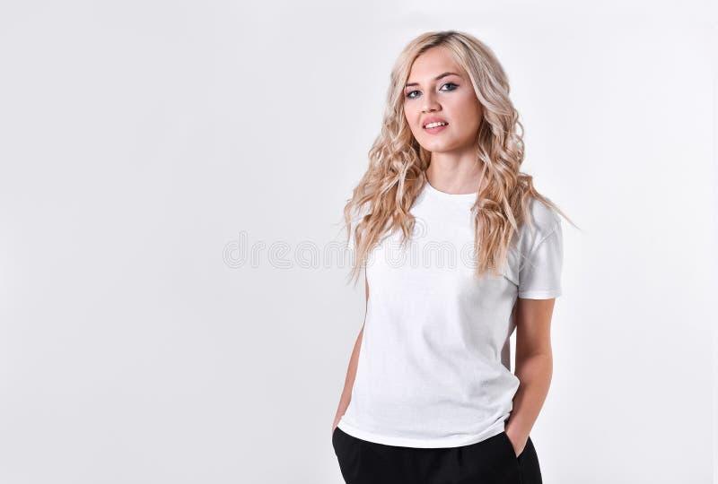 Eine junge schöne Mädchenblondine steht mit den gefalteten Händen stockfoto