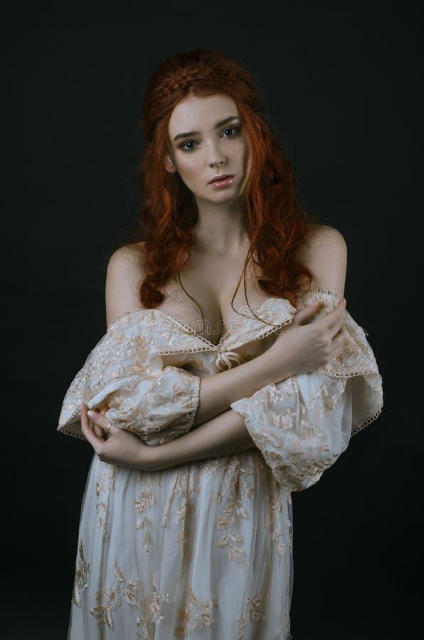 Eine junge schöne rothaarige Frau in einem langen Weinlesegoldkleid, das auf einem schwarzen Hintergrund aufwirft Eine Prinzessin lizenzfreie stockfotografie