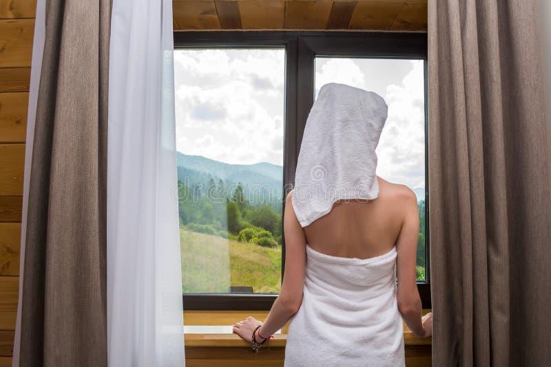 Eine junge, schöne, sexy Frau, nachdem eine Dusche, Stände eingewickelt in einem Tuch nahe dem Fenster im Hotel mit Blick auf den lizenzfreies stockbild