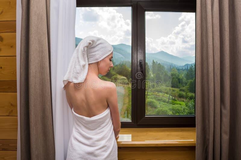 Eine junge, schöne, sexy Frau, nachdem eine Dusche, Stände eingewickelt in einem Tuch nahe dem Fenster im Hotel mit Blick auf den lizenzfreie stockfotos