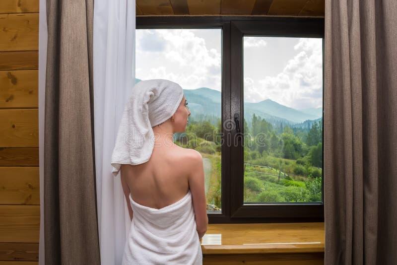 Eine junge, schöne, sexy Frau, nachdem eine Dusche, Stände eingewickelt in einem Tuch nahe dem Fenster im Hotel mit Blick auf den lizenzfreie stockfotografie