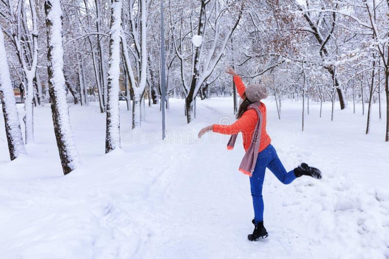 Eine junge Schönheit geht in Winter entlang einer Gasse in einem schneebedeckten fabelhaften Stadtpark lizenzfreie stockfotografie