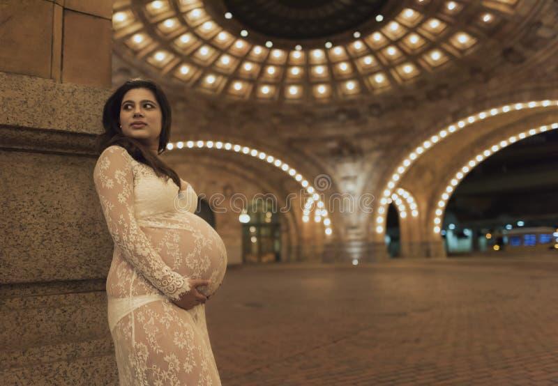 Eine junge schwangere Frau, die vor einem alten Erbgebäude steht stockfotos