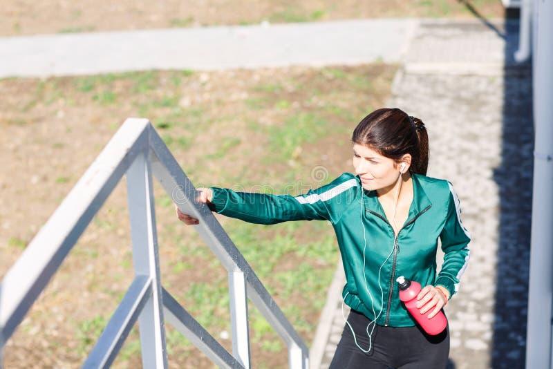 Eine junge sportliche Frau mit dem perfekten Körper, der Übungen auf der Treppe im Freien tut stockbild