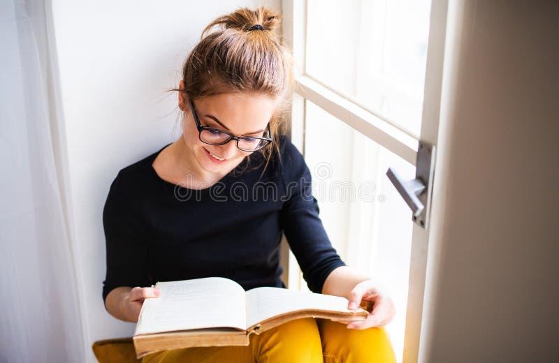 Eine junge Studentin mit dem Buch, das auf dem Fensterbrett, studierend sitzt stockfoto