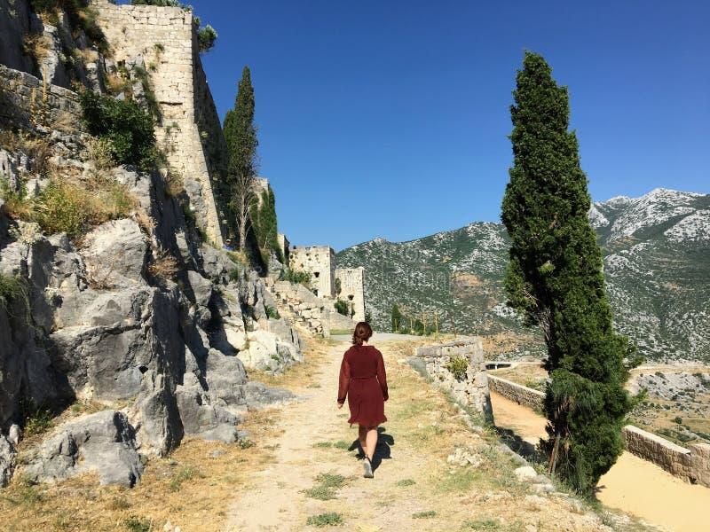 Eine junge Touristenfrau, die an einem schönen Sommertag durch die mittelalterliche Festung Klis spaziert lizenzfreie stockfotos