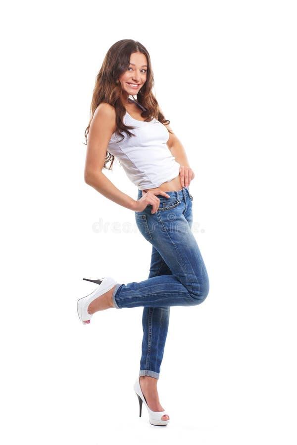 Eine junge und glückliche Brunettefrau in den stilvollen Jeans stockbild