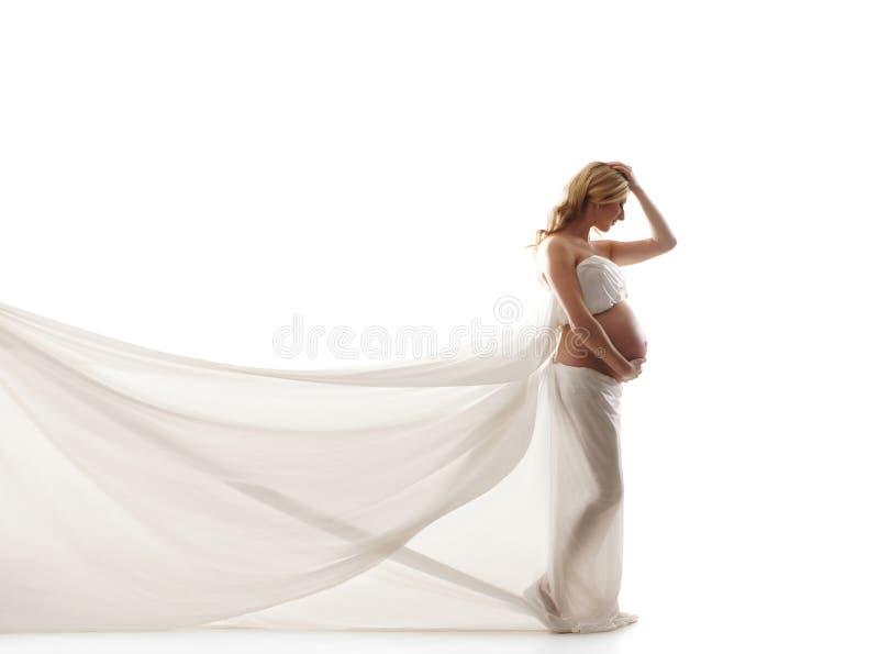 Eine junge und schwangere blonde Frau in der weißen Seide lizenzfreies stockfoto