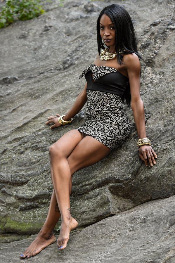 Eine junge weibliche Afroamerikanerfrau, die das elegante Kleid aufwirft im Park trägt stockbilder