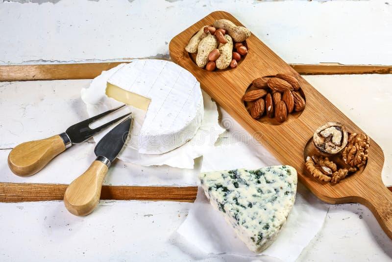 Eine Käseservierplatte, die blaue Ader- und Camembertkäse auf dem hölzernen Hintergrund, Draufsicht kennzeichnet stockfotografie